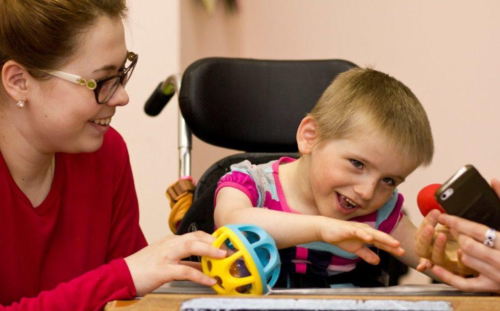 Ein Kind mit eingeschränkten motorischen Fähigkeiten sitzt in einem Rollstuhl an einem Tisch – es lacht. Neben ihm sitzt eine Betreuerin und hält ihm einen bunten Ball hin.