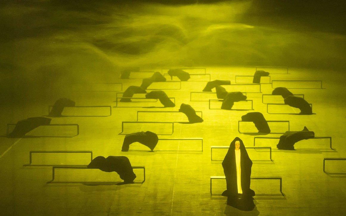 """Szene aus der Inszenierung """"De Materie"""" bei der Ruhrtriennale 2014: Auf einer sehr großen Bühne stehen circa zwanzig schmale Bänke, von einigen hängen komplett in schwarzen Stoff gehüllte Körper. Im Vordergrund steht eine in eine schwarze Kutte gehüllte Person und schaut ins Publikum. Nebel wabert über die Bühne, die Szene ist in unheimlich wirkendes gelbes Licht getaucht. Über das Bild läuft der Schriftzug """"Ich ward äuszerlich befridigt und ganz erfüllet"""" – ein Zitat aus """"De Materie""""."""