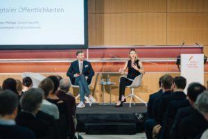 Prof. Dr. Whitney Phillips und Dr. Cornelius Puschmann sitzen auf der Bühne.