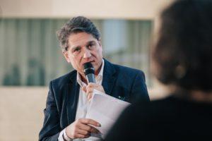 Jakob Augstein mit einem Mikrofon in der Hand