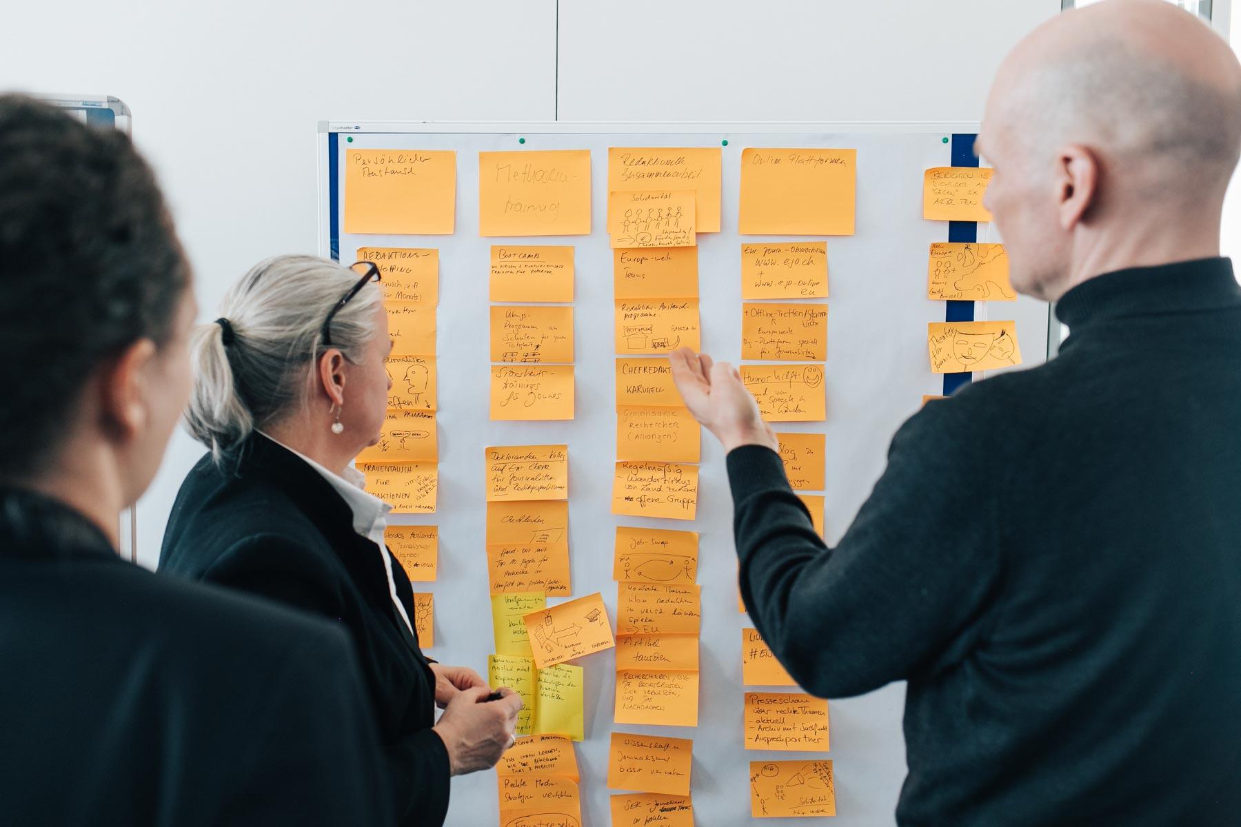 Drei Teilnehmer*innen stehen vor einer Moderationswand und diskutieren über die dort befestigten Post-Its mit Ideen.