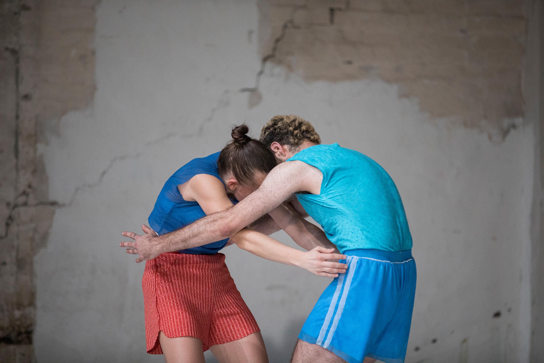 Eine Tänzerin und ein Tänzer umarmen sich auf der Bühne.