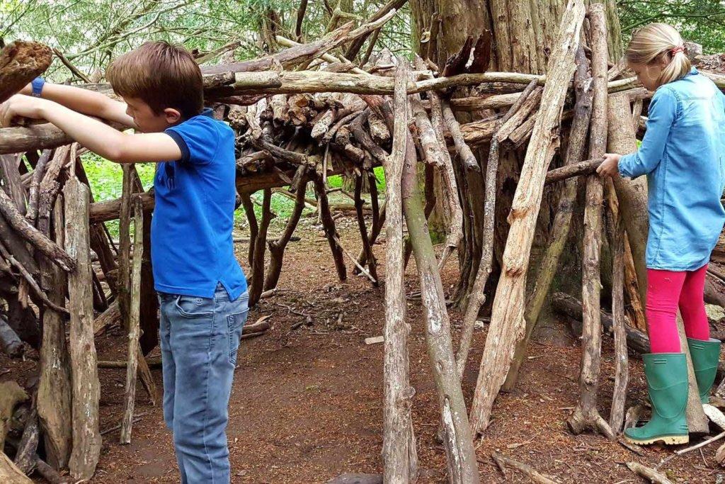Kinder spielen mit Ästen im Wald